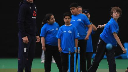 Sam Billings of England looks on as a young kid gets ready to bowl during an ICC Champions Trophy Cricket for Good clinic at Birmingham.