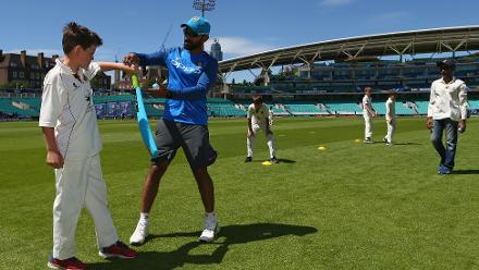 Dinesh Karthik coaches local children during the ICC Cricket For Good coaching session with India at The Oval