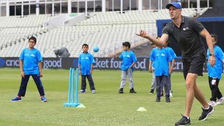 Children look on as Mike Hussey throws a ball at the Cricket For Good coaching clinic at Birmingham.