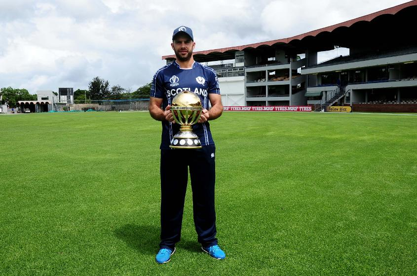 Scotland Captain Kyle Coetzer holding the ICC CWCQ Trophy at Queens Sports Club.