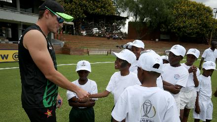 Zimbabwe players greet the children during a Cricket For Good session