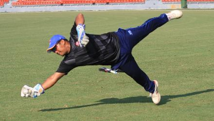 Shafiq Sharif, the Malaysian wicketkeeper, practices before the start of the game