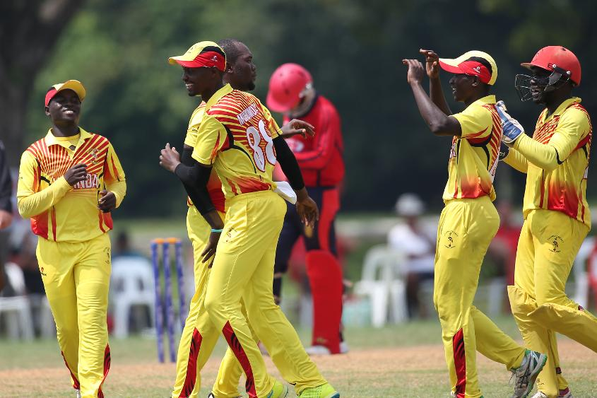Uganda players celebrate the fall of a Jersey wicket