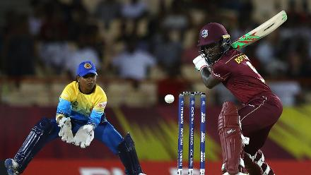 Deandra Dottin of Windies hits the ball towards the boundary, as Dilani Manodara of Sri Lanka looks on during the ICC Women's World T20 2018 match between Windies and Sri Lanka at Darren Sammy Cricket Ground on November 16, 2018.
