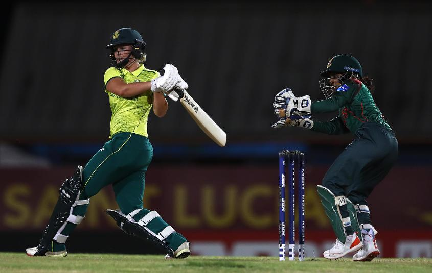 Dane van Niekerk of South Africa hits the ball towards the boundary, as Nigar Sultana of Bangladesh looks on during the ICC Women's World T20 2018 match between South Africa and Bangladesh at Darren Sammy Cricket Ground on November 18, 2018.