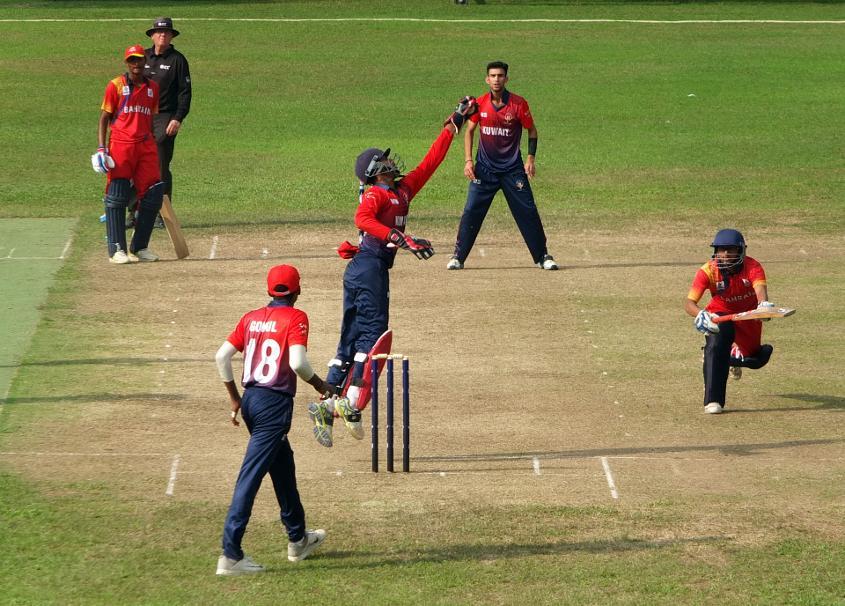 A Bahrain batsman stretches for the crease