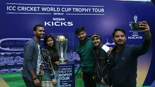 Fans pose with the prized trophy during the ICC CWC Trophy Tour driven by Nissan Kicks