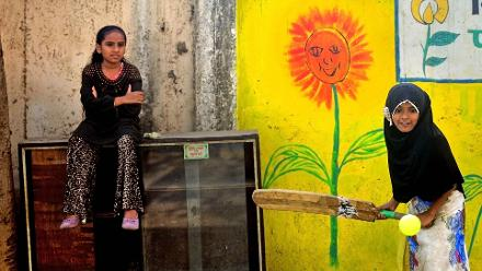 Shortlisted - SL Shanth: A Mumbai girl shapes up to hit the ball in a game of street cricket while her friend looks on keenly