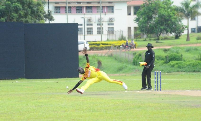 Uganda's Charles Waiswa is in a full stretch as he tries to stop a ball off his own bowling