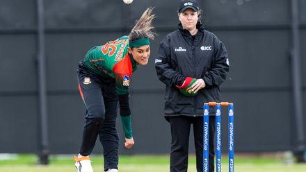 Bangladesh's Jahanara Alam bowls next to a stoic Umpire, Eloise Sheridan, from Australia.
