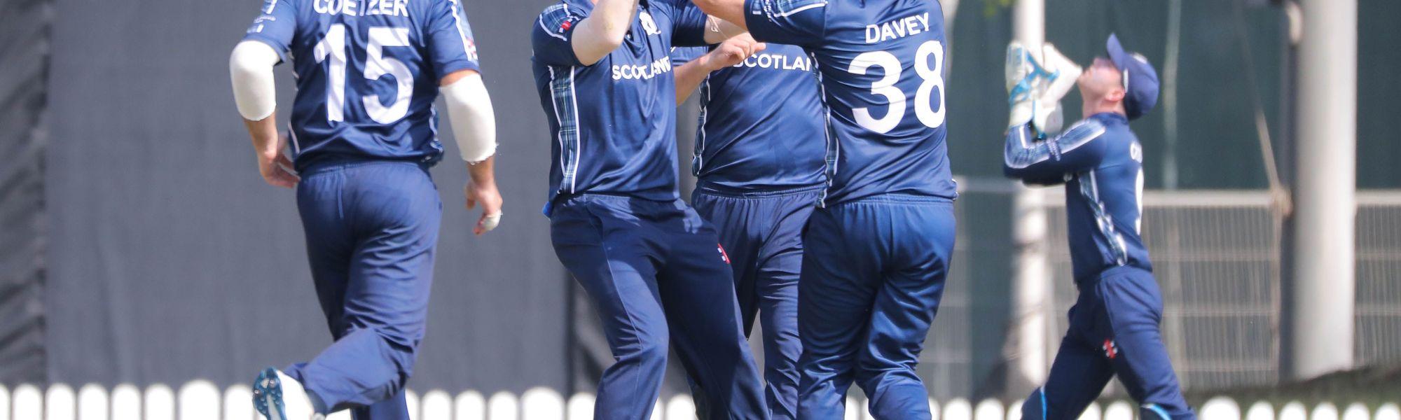 Scotland celebrate a wicket.