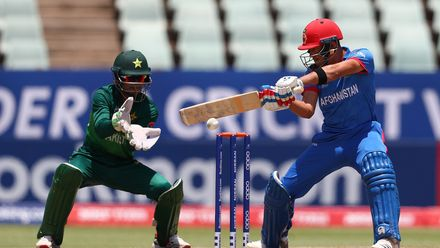 Abdul Rahman Rahmani of Afghanistan hits the ball towards the boundary, as Rohail Nazir of Pakistan looks on during the ICC U19 Cricket World Super League Quarter Final match between Afghanistan and Pakistan at Willowmoore Park on January 31, 2020.