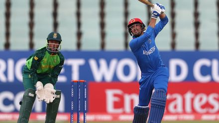 Ibrahim Zadran of Afghanistan hits the ball towards the boundary, as Khanya Cotani of South Africa looks on during the ICC U19 Cricket World Cup 7th Place Play-Off match between South Africa and Afghanistan at Willowmoore Park on February 05, 2020.