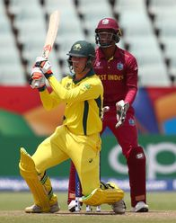 Mackenzie Harvey of Australia hits the ball towards the boundary, as Leonardo Julien of West Indies looks on during the ICC U19 Cricket World Cup 5th Place Play-Off match between West Indies and Australia at Willowmoore Park on February 07, 2020.