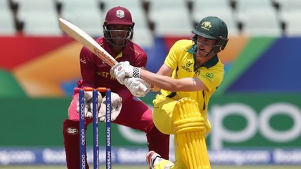 Lachlan Hearne of Australia hits the ball towards the boundary, as Leonardo Julien of West Indies looks on during the ICC U19 Cricket World Cup 5th Place Play-Off match between West Indies and Australia at Willowmoore Park on February 07, 2020 in Benoni.