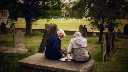 Shortlist - Derek Payne: A couple enjoy afternoon tea in the graveyard of St Anne's church while watching cricket on Kew Green, close to the Royal Botanic Gardens
